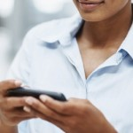 African American business executive text messaging on cell phone