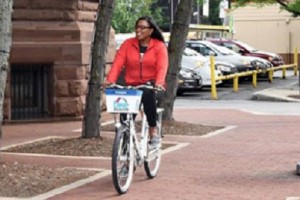 Mayor Lovely Warren riding one of the city's new Zagster bikes.
