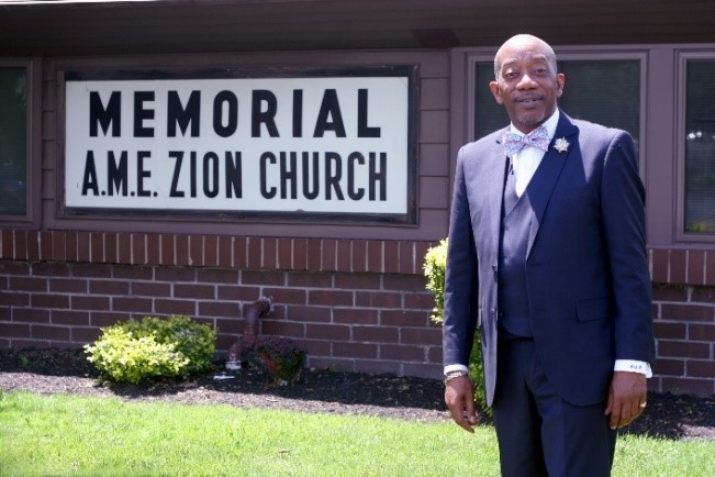 Rev. Dr. Kenneth Q. James stands in front of today's Memorial AME Zion Church at